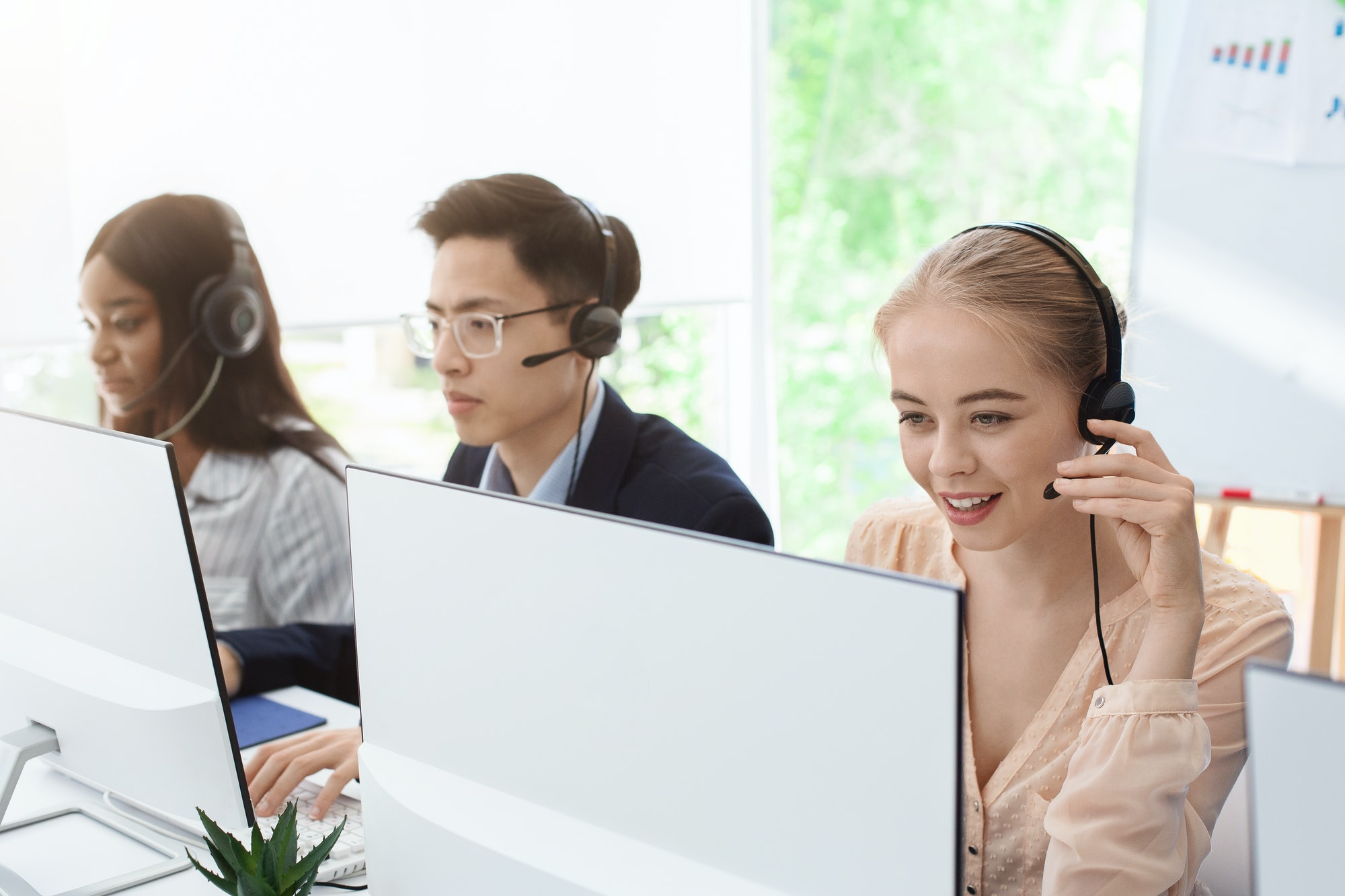 Group of young operators with headsets working at call centre