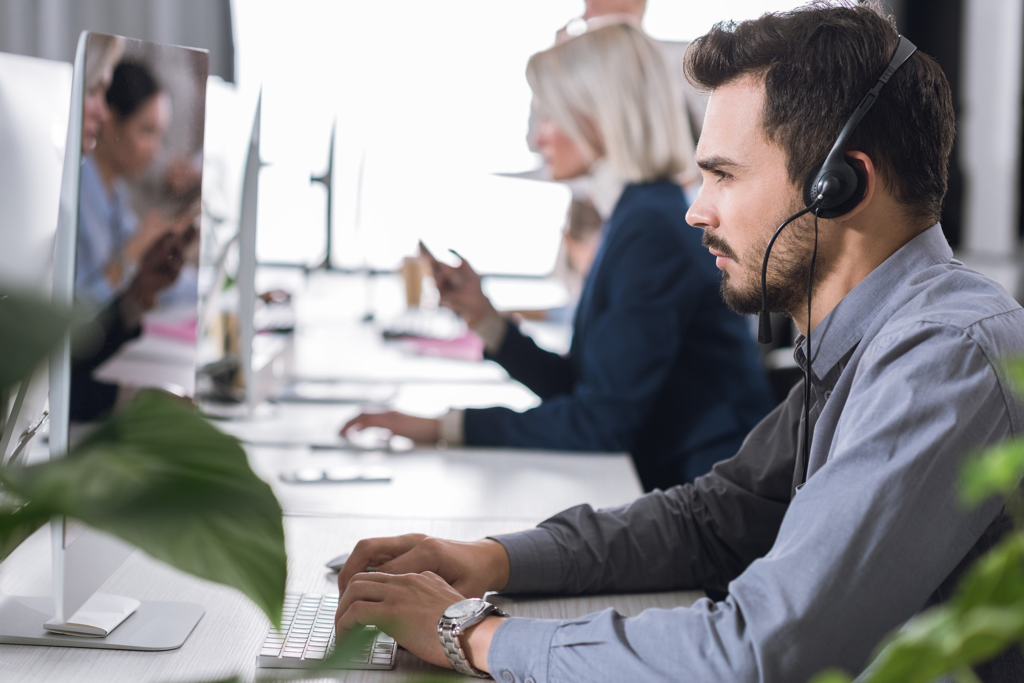 selective focus of focused call center operator in headset working in office